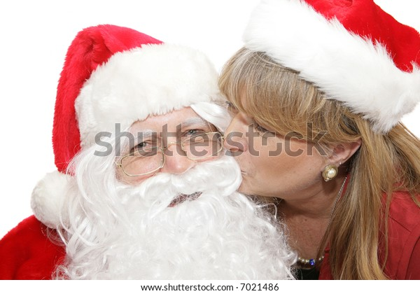 Santa smiles as he receives a kiss from a pretty blond woman.  White background.