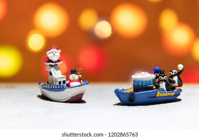 Santa and Snow man on one boat with three penguins on the other boat