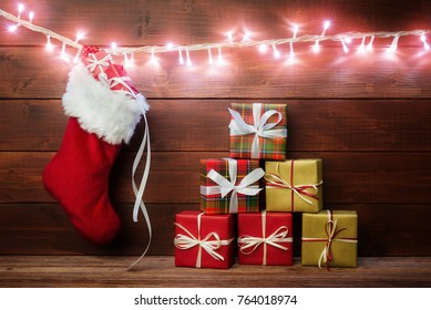 Santa sock with gift boxes over dark wooden background.