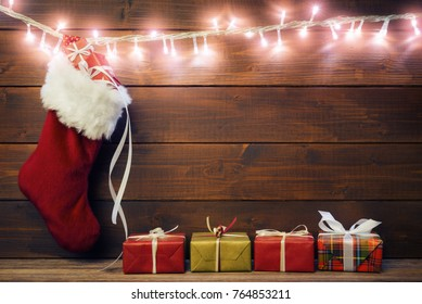 Santa sock and gift boxes over dark wooden background with copy space.