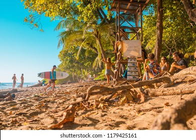 Santa Teresa, Costa Rica - June, 28, 2018: Toursist sirtring in the sand and enjoying the beautiful view of Santa Teresa beach, and some surfers check out the conditions to surf