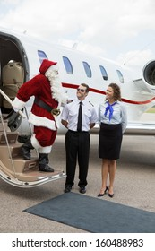 Santa thanking pilot and airhostess while standing on ladder of private jet