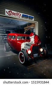 Santa tuning his hot rod in the door of his speed shop.