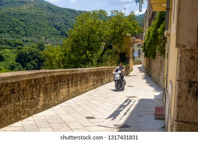 Sant'Agata de' Goti, Benevento / Italy - 07 19 2018: A young adult drives a motorcycle in Sant'Agata de' Goti, a stunning Medieval village with a view on the surrounding hills.