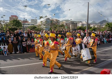 "SANTA-KRUZ-DE-TENERIFE, SPAIN - March 6, 2014: Orchestra in yellow suits marching in front of the audience. The theme of the carnival ""Cartoons."" The carnival is held annually in February-March."