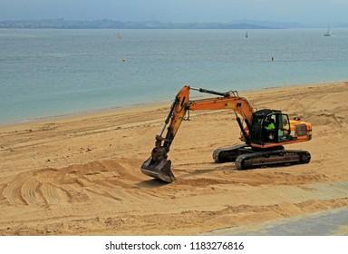 Santander, Spain - May 26, 2018: excavator working on the beach in Santander, Spain