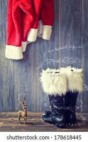 Santa's black boots with fur trim and hanging jacket