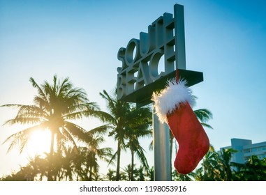Santa's Christmas stocking hanging from South Beach sign in Miami with a tropical palm tree sunrise backdrop