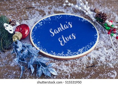Santa's Elves Written In Chalk On Blue Chalkboard Holiday Sign Background With Snow And Decorations.