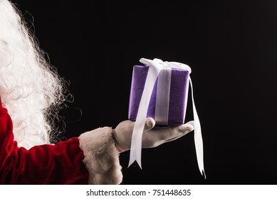 Santa's hand holding Christmas gift,Purple present box in the hands of Santa Claus with black background, Merry Christmas and happy New Year concept,Christmas decoration holiday party, winter holiday.