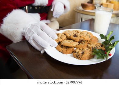 Santa's hand reaching in to take a chocolate chip cookie from a plate