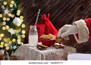 santa`s hand taking a cookie from little table standing in the room with christmas tree and gift boxes around it