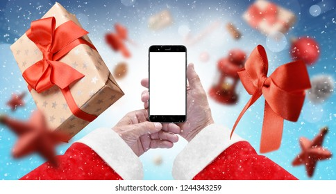 Santa's hands holding black phone with isolated screen on blue background surrounded with gift box, red ribbon and xmas tree ornaments. Mockup