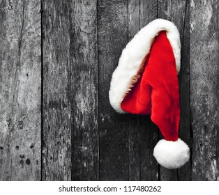 Santa's hat hanging on a desaturated grunge wood background.