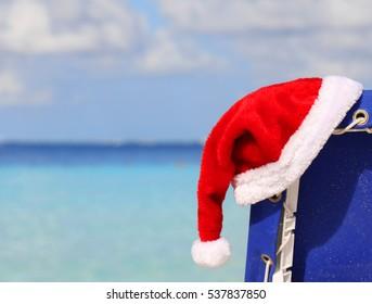 Santa's Hat on chair lounge on tropical caribbean beach. Christmas
