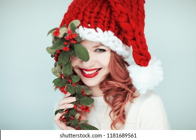 Santas little helper. Beautiful happy young woman with a santa claus hat, perfect make up, red lipstick, holding branch with red berries