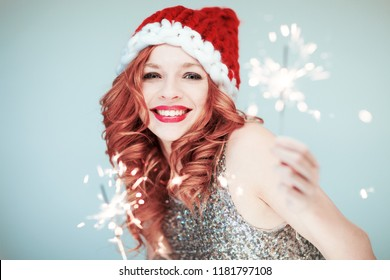 Santas little helper. Beautiful happy young woman with a santa claus hat, perfect make up, red lipstick, holding sparkler lights
