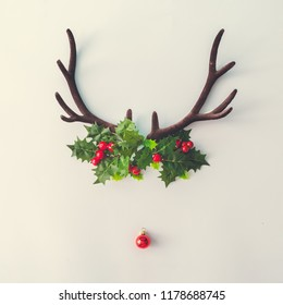 Santas reindeer made of antlers, Holly Christmas plant and red New Year bauble decoration. Minimal winter holiday concept.
