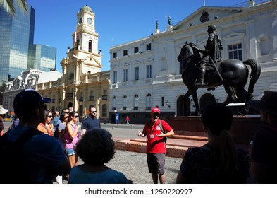 Santiago, Chile - 25 November, 2018: Tourists at free guided tour next to monument of Pedro de Valdiviva on his horse on Plaza de las Armas square in city center
