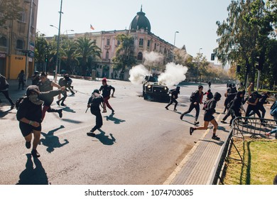 Santiago, Chile - April 19, 2018:  Riot police vehicle sprays tear gas to demonstrators during a demonstration demanding an end to the Profit in the Education.