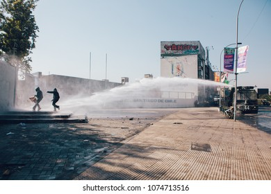Santiago, Chile - April 19, 2018: Chilean police water cannon disperse protesters during a demonstration demanding an end to the Profit in the Education.