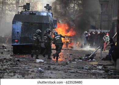 Santiago, Chile - August 09, 2011: water cannon truck and riot police disperse demonstrators who burned a car during a student strike in Santiago's Downtown, Chile.