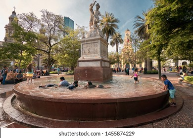 Santiago, Chile, Circa 2019: Kids having so much fun in a traditional summer bathing at Simon Bolivar 's monument known as Plaza de Armas Fountain near Paseo Ahumada and Main Square