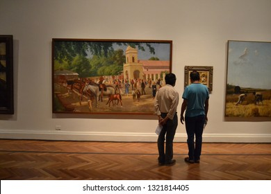 Santiago, Chile / Chile - Fabruary 24 2019: A growing number of people is visiting the Museum of Fine Arts in Santiago de Chile. Two  persons are admiring one of the main paintings of the exposition.