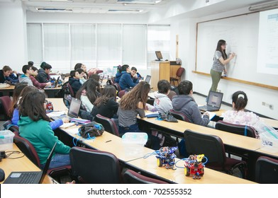 Santiago, Chile. July 21, 2017. Group of small  unknown students in robotic scientific activities next to professor.