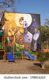 SANTIAGO, CHILE - JUNE 13, 2014: Colourful murals adorning the walls of tenement blocks in the San Miguel area of Santiago, Chile. The murals were created to revitalise this once run down area.
