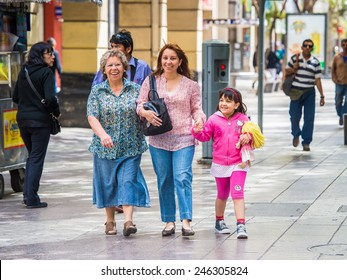 SANTIAGO, CHILE - NOV 1, 2014:  Unidentified Chilean family walks in Santiago. Chilean people are mainly of mixed Spanish and Amerindian descent