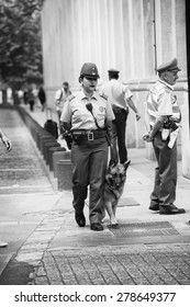 SANTIAGO, CHILE - NOV 1, 2014:  Unidentified Chilean police woman with a dog in Santiago. Chilean people are mainly of mixed Spanish and Amerindian descent