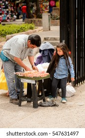 SANTIAGO, CHILE - NOV 1, 2014:  Unidentified Chilean woman girl buys something in the street. Chilean people are mainly of mixed Spanish and Amerindian descent