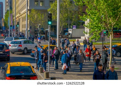 SANTIAGO, CHILE - SEPTEMBER 13, 2018: Outdoor view of Traffic flow on streets of Santiago with crowd of people walking in the sidewalk in rush hour in Chile, South America