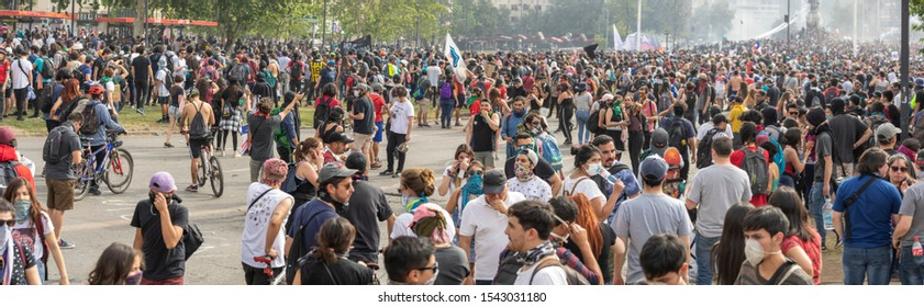Santiago de Chile Chile 23/10/2019 People crowds protesting at Santiago de Chile streets in Plaza de Italia during latest Chile protests and general strike. Police repeal the crowd with tear gas