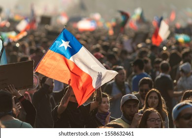 Santiago de Chile Chile 29 October 2019 People crowds protesting at Santiago de Chile streets in Plaza de Italia during latest Chile protests and general strike. Police repeal the crowd with tear gas