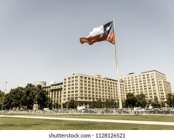 SANTIAGO DE CHILE - JANUARY 26, 2018: Chileans walking near the giant flag on Avenida La Alameda with the citizenship Square, in downtown Santiago de Chile. Image with vintage and yesteryear effect