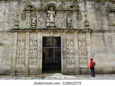 Santiago de Compostela, Spain - Apr 21, 2011: Pilgrim at the Gate of Forgiveness (Puerta del Perdon) at the Cathedral of Santiago de Compostela, Way of St. James (Camino de Santiago), Spain