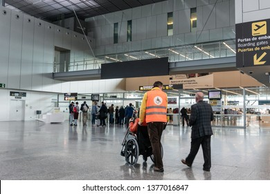 Santiago de Compostela, Spain. April 19 2019: Airport staff pushing pushing elderly people in wheelchair in the airport of Santiago de Compostela