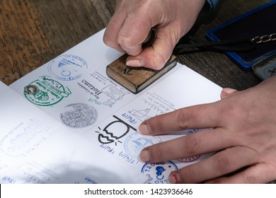 Santiago de Compostela, Spain; April 19, 2019: Pilgrim stamping a identification named The Compostela the accreditation of the pilgrimage to the Tomb of St. James. Camino de Santiago