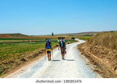 Santiago de Compostela, Spain - October 15, 2011: Pilgrims walking in dry countryside in Northern Spain, Europe. Famous Camino de Santiago walking road, path and street. Pilgrims ways.