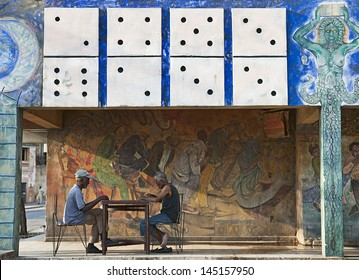 SANTIAGO DE CUBA, CUBA - APRIL 12, 2009: Old men playing dominoes on the patio of an old painted house in Santiago de Cuba, Cuba on April 12, 2009. The domino game is the most  practiced in Cuba.