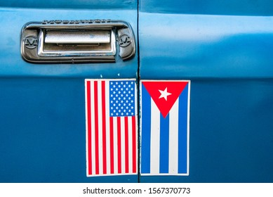 Santiago de Cuba, Cuba-July 5, 2019: United States flag alongside the Cuban National Flag in the door of an old Russian Moskvich car. After the detente of Obama the image became common in the island