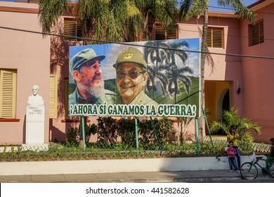 Santiago de Cuba, Cuba - January 12, 2016:  streets in the center of Santiago de cuba - Big poster of Raul and Fidel Castro. people walking around. Santiago is the 2nd largest city in Cuba