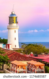 Santiago de Cuba: Lighthouse on the shore of coastal Cuban city in sunset or dusk. The place is a tourist attraction.