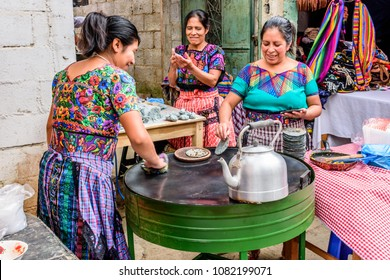 Santiago Sacatepequez, Guatemala - November 1, 2017: Local Maya women dressed in traditional clothing make corn tortillas in the street during the giant kite festival on All Saints' Day.