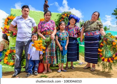 Santiago Sacatepequez, Guatemala - November 1, 2017: Indigenous family in traditional clothing hold flowers to decorate graves of loved ones in cemetery & venue for giant kite festival, All Saints Day