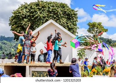 Santiago Sacatepequez, Guatemala - November 1, 2017: Kids fly kites from tombtops during Giant kite festival honoring spirits of the dead in town cemetery on All Saints Day.