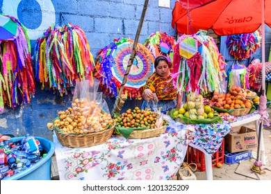 Santiago Sacatepequez, Guatemala - November 1, 2017: Selling fruit & handmade kites in street as crowds head to giant kite festival honoring spirits of the dead in cemetery on All Saints Day.