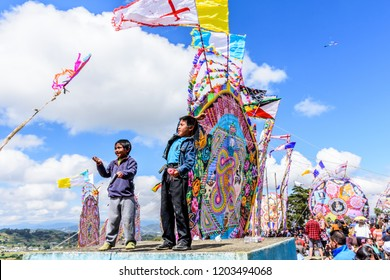 Santiago Sacatepequez, Guatemala - November 1, 2017: Boys fly kites from tombtops during Giant kite festival honoring spirits of the dead in town cemetery on All Saints Day.